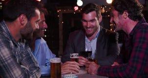 Grupo de amigos masculinos que se relajan junto en la barra del tejado almacen de metraje de vídeo