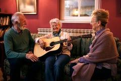 Grupo de amigos mayores que tocan la guitarra y que se divierten en el oficio de enfermera imágenes de archivo libres de regalías