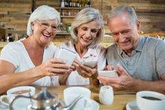 Grupo de amigos mayores que usan los teléfonos móviles Imagen de archivo libre de regalías