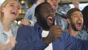 Grupo de amigos multiétnicos en barra que celebran a la liga preferida de la meta del equipo de deportes metrajes
