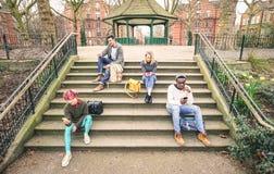 Grupo de amigos multirraciais que usam o telefone esperto móvel - conceito do apego fotografia de stock royalty free
