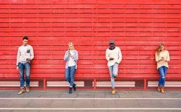 Grupo de amigos multirraciales de la moda que usan smartphone Imagen de archivo
