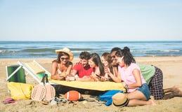 Grupo de amigos multirraciales que se divierten así como smartphone fotografía de archivo libre de regalías