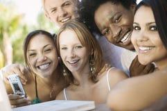 Grupo de amigos na tabela do pátio traseiro usando o fim do retrato do portátil e do telemóvel acima Imagem de Stock