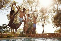 Grupo de amigos nas férias que saltam na associação exterior fotos de stock royalty free