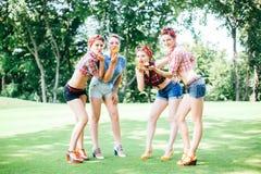 Grupo de amigos no parque que tem o partido do divertimento Meninas alegres com bolos nas mãos Fotos de Stock Royalty Free