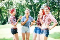 Grupo de amigos no parque que tem o partido do divertimento Meninas alegres com bolos nas mãos Estilo retro Fotos de Stock