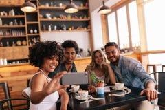 Grupo de amigos no restaurante que toma o selfie fotografia de stock