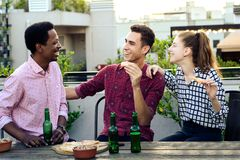 Grupo de amigos novos com pizza e garrafas da bebida imagem de stock