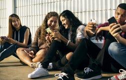 Grupo de amigos novos do adolescente que refrigeram para fora junto usando o conceito social dos meios do smartphone imagens de stock royalty free