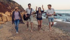 Grupo de amigos novos e alegres que andam na praia foto de stock