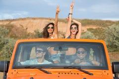 Grupo de amigos novos entusiasmado que estão em um carro com as mãos levantadas imagens de stock royalty free