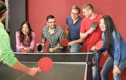 Grupo de amigos novos felizes que jogam o tênis de mesa do pong do sibilo Imagem de Stock Royalty Free