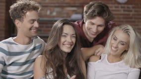 Grupo de amigos novos felizes que sentam-se em um sofá que compartilha de um tablet pc filme
