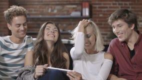 Grupo de amigos novos felizes que sentam-se em um sofá que compartilha de um tablet pc video estoque