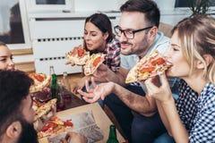 Grupo de amigos novos que comem a pizza imagem de stock royalty free
