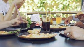 Grupo de amigos novos que comem a pizza em um exterior filme