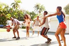 Grupo de amigos novos que jogam o fósforo de basquetebol Imagens de Stock Royalty Free