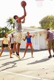 Grupo de amigos novos que jogam o fósforo de basquetebol Fotografia de Stock
