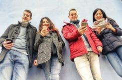 Grupo de amigos novos que olham seus smartphones na cidade velha fotos de stock