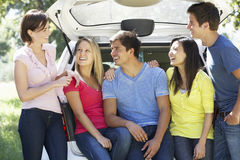 Grupo de amigos novos que sentam-se no tronco do carro Fotografia de Stock Royalty Free