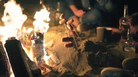 Grupo de amigos novos que sentam-se pelo fogo tarde na noite, grelhando salsichas e bebendo a cerveja, falando e tendo o divertim video estoque