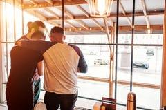 Grupo de amigos que abrazan y que comprueban imágenes en smartphone en barra del salón Hombres jovenes que se divierten imágenes de archivo libres de regalías