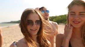 Grupo de amigos que andam na praia ensolarada Os jovens bronzearam-se os povos caucasianos alegres que andam, conversando e rindo vídeos de arquivo