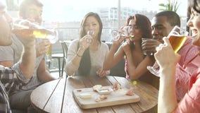 Grupo de amigos que apreciam a bebida e o petisco na barra do telhado video estoque