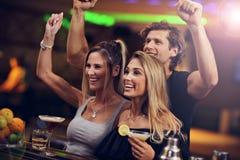 Grupo de amigos que apreciam a bebida na barra imagem de stock royalty free