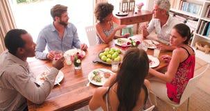 Grupo de amigos que apreciam o partido de jantar em casa junto video estoque