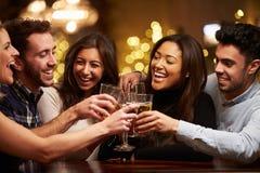 Grupo de amigos que apreciam que nivela bebidas na barra