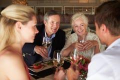 Grupo de amigos que apreciam a refeição no restaurante foto de stock