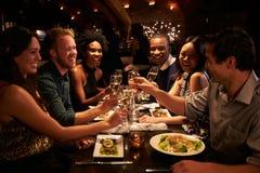 Grupo de amigos que apreciam a refeição no restaurante fotos de stock