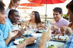 Grupo de amigos que apreciam a refeição no restaurante exterior imagem de stock royalty free