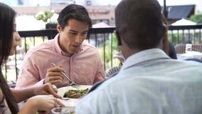Grupo de amigos que apreciam a refeição no restaurante exterior filme