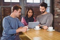 Grupo de amigos que apreciam um café com uma tabuleta Imagem de Stock