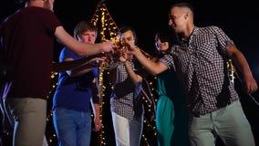 Grupo de amigos que bailan y que tienen bebidas en el partido al aire libre de la noche almacen de metraje de vídeo