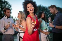 Grupo de amigos que beben, charlando y divirti?ndose en el partido al aire libre fotos de archivo libres de regalías