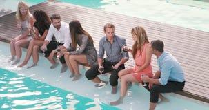 Grupo de amigos que beben con el pie en piscina almacen de metraje de vídeo
