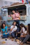 Grupo de amigos que beben la cerveza mientras que almorzando Foto de archivo libre de regalías