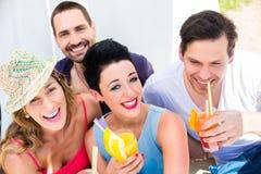 Grupo de amigos que beben los cócteles en barra de la playa fotos de archivo