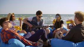 Grupo de amigos que beben los cócteles y la cerveza y que hacen las alegrías que se sientan en easychairs en la playa y que escuc metrajes