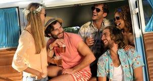 Grupo de amigos que beben un poco de cerveza y que se sientan en la furgoneta almacen de metraje de vídeo