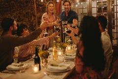 Grupo de amigos que brindam bebidas em um partido imagens de stock royalty free