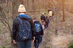 Grupo de amigos que caminan con las mochilas en bosque de la primavera de la parte posterior Backpackers que caminan en el bosque Imágenes de archivo libres de regalías
