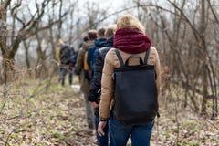 Grupo de amigos que caminan con las mochilas en bosque de la primavera de la parte posterior Backpackers que caminan en el bosque Imagen de archivo