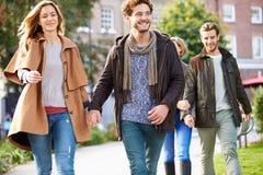 Grupo de amigos que caminan a través de parque de la ciudad junto Imagen de archivo libre de regalías