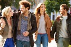 Grupo de amigos que caminan a través de parque de la ciudad junto Foto de archivo libre de regalías