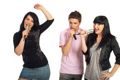 Grupo de amigos que cantan con los micrófonos Imagen de archivo libre de regalías